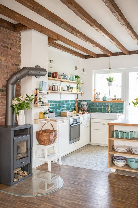 a welcoming neutral kitchen with blue subway tiles, wooden beams and shelving and a hearth next to it