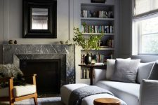 a welcoming neutral living room with a grey marble fireplace and neutral furniture invites people in