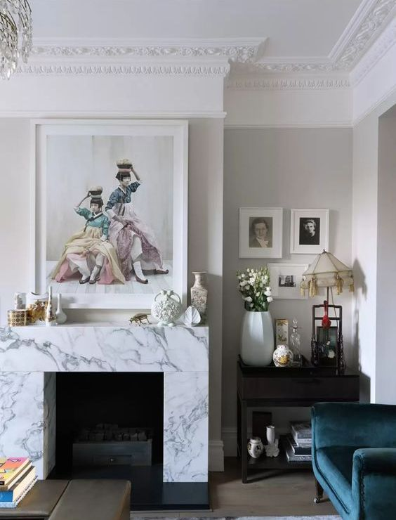 a whimsical vintage-inspired living room with a non-working fireplace clad with white marble and beautiful artworks