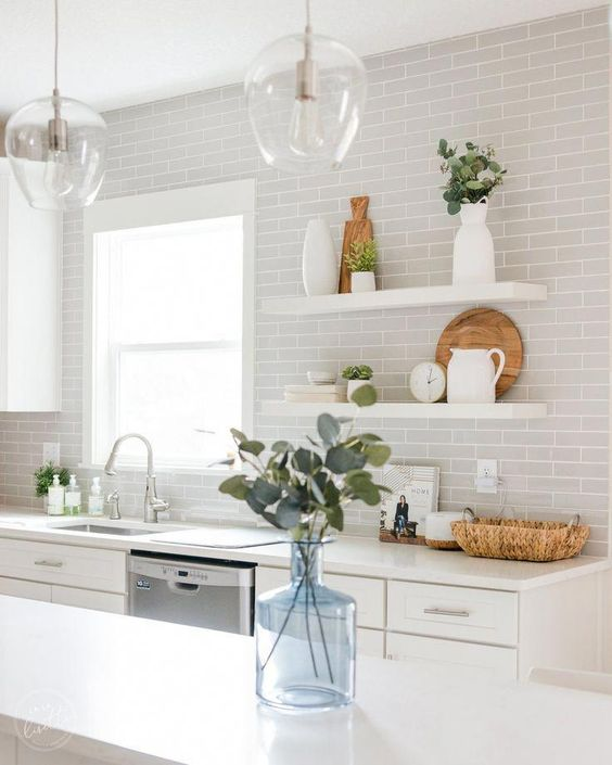 a white kitchen finished off with dove grey subway tiles and touches of greenery looks fresh and ethereal