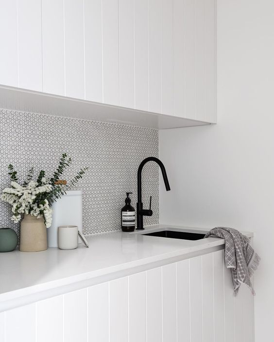 a white kitchen with a white penny tile backsplash and black fixtures for an ultra-modern look