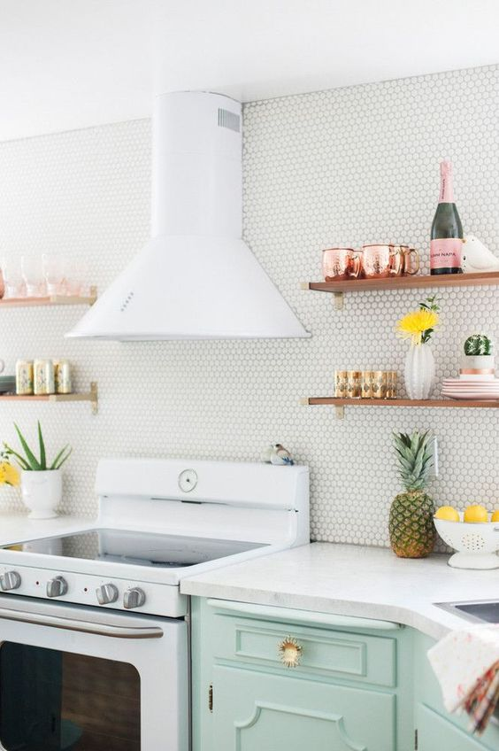a white penny tile backsplash paired with a white stone countertop and wooden shelves create a chic look