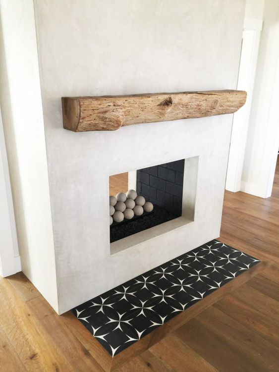a white two-sided concrete fireplace with mosaic tiles and a rough wooden mantel is very bold and cool