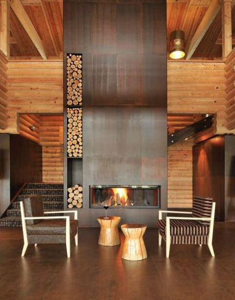 a woodland foyer with an oversized aged metal clad fireplace with niches for storing firewood is wow