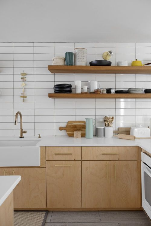 an airy Scandinavian kitchen with light colored wooden cabinets and shelves, a white stacked tile wall and brass fixtures