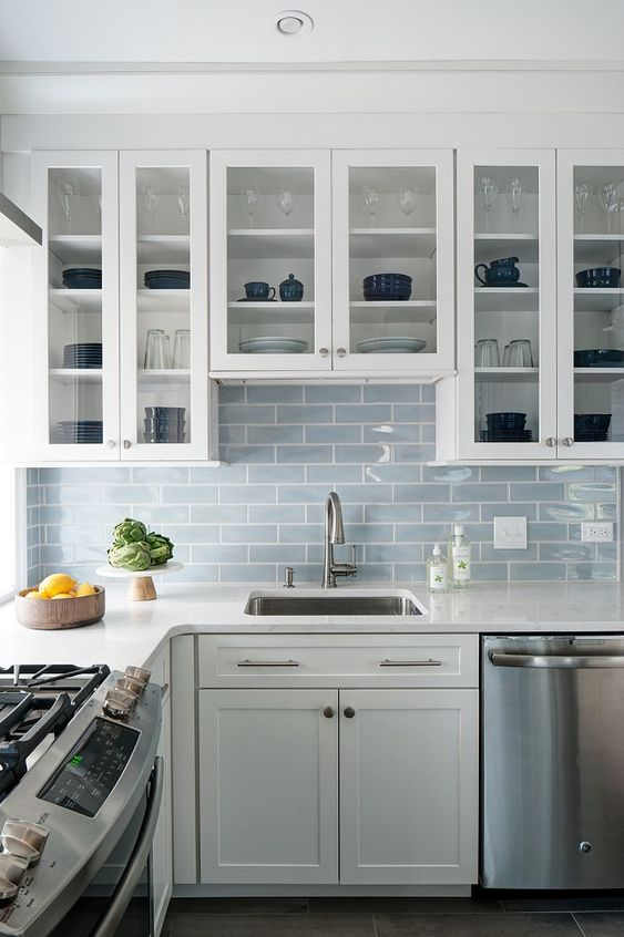 an airy white kitchen with a light blue subway tile backsplash and neutral metallics is very welcoming