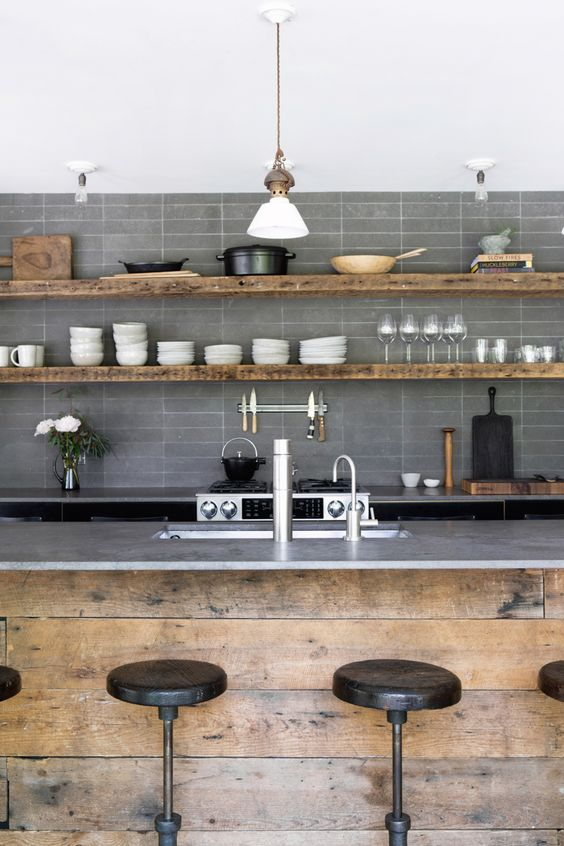 an industrial kitchen with matte grey stacked tiles, rough wood furniture and pendant lamps