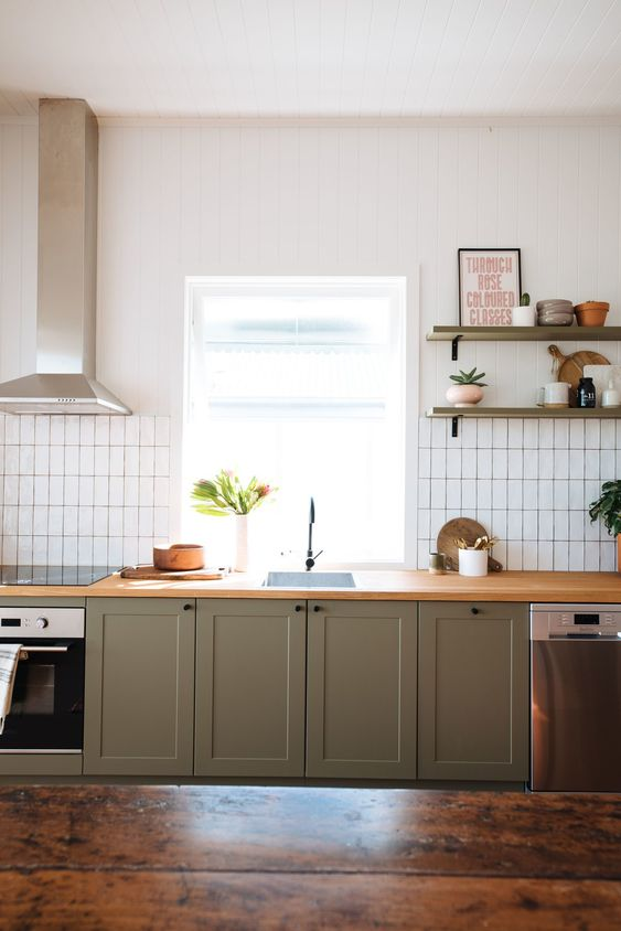 an olive green kitchen with wooden countertops, a white stacked tile backsplash and olive green shelves