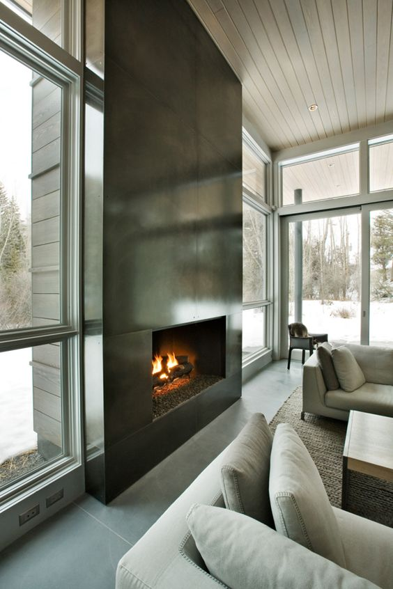 an ultra-modern fireplace clad with dark metal sheets looks very eye-catching and even show-stopping