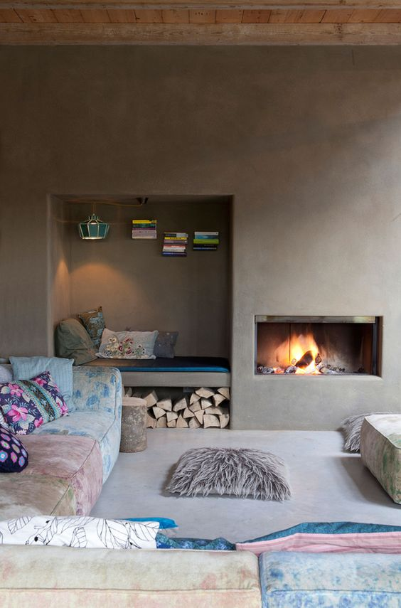 an unusual living room with concrete walls and a built-in fireplace, a niche for storage and a daybed, colorful furniture