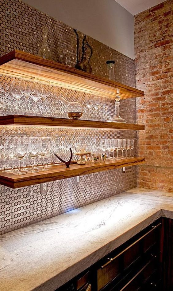 copper penny tiles perfectly pair with wooden shelves with lights and give much color to the space