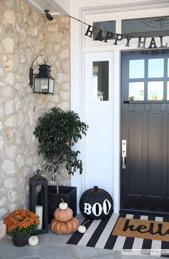 modern rustic Halloween porch decor with stacked pumpkins, a candle lantern and potted plants and blooms