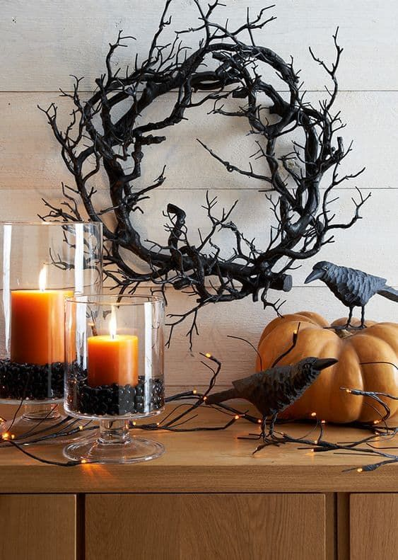 rustic Halloween decor with a scary vine wreath, blackbirds, rust-colored candles in black beans and lights