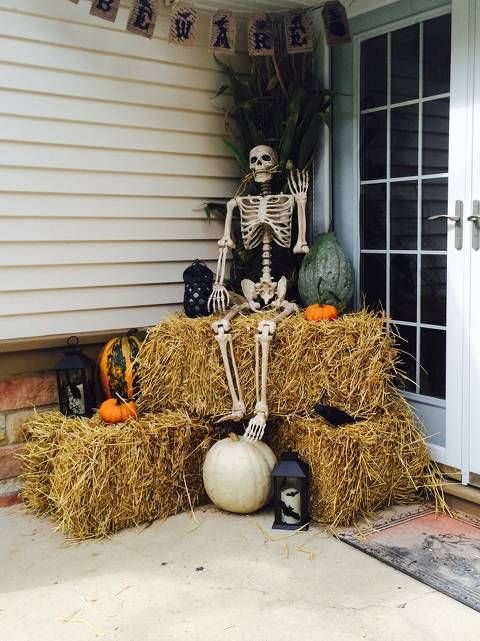 rustic Halloween decor with hay, bat candles, natural pumpkins, a skeleton and some husks plus a burlap bunting