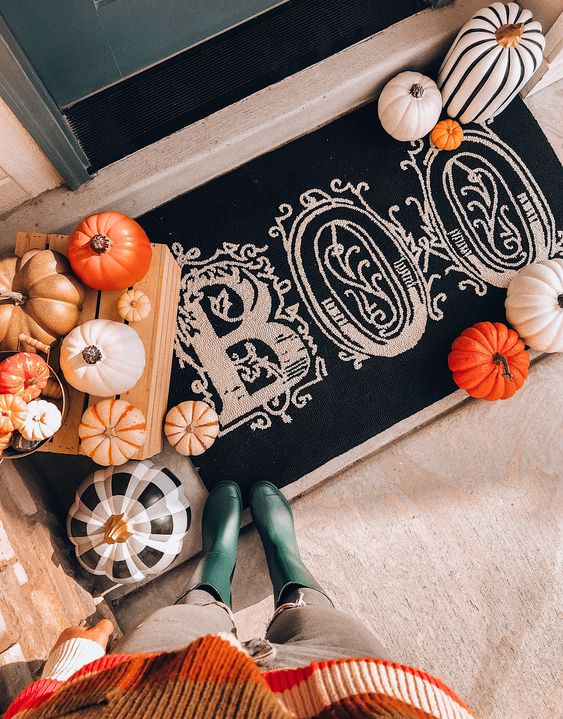 rustic front porch Halloween decor with natural pumpkins, a black and white rug and painted faux pumpkins