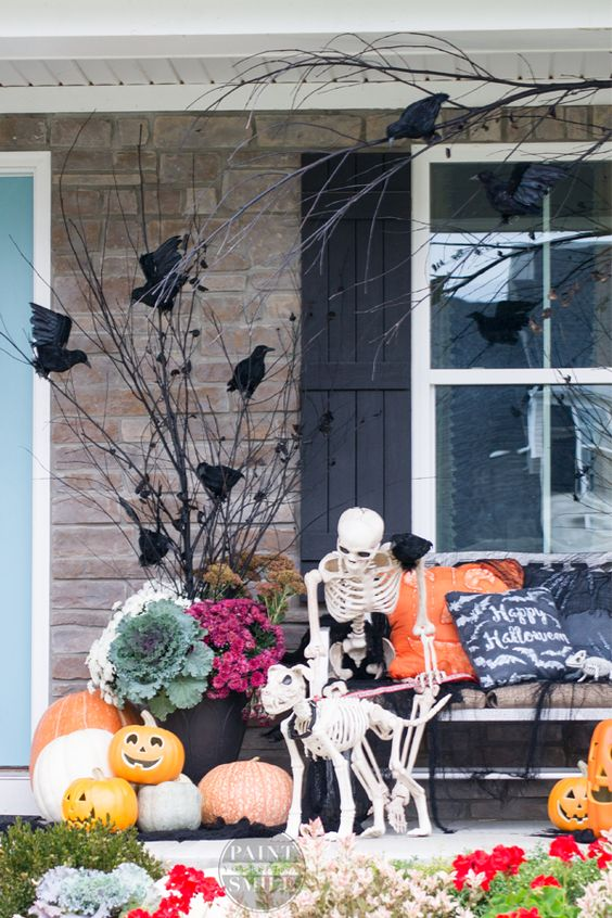 rustic outdoor Halloween decor with blackbirds, bright blooms and veggies, pumpkins, skeletons and branches