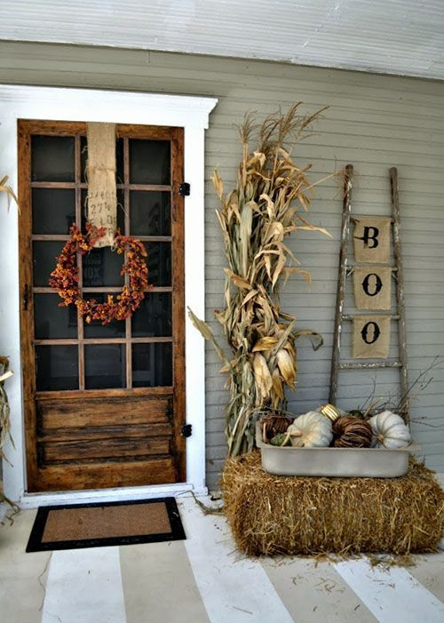 vintage rustic Halloween decor wiht a fall leaf wreath, hay, pumpkins in a tray and corn husks