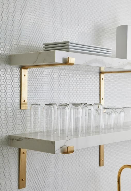 white penny tiles, white marble shelves and gold fixtures for a chic contemporary look