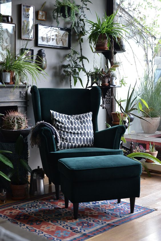 a bold boho nook with a dark green wingback chair and a matching footrest, lots of greenery, cacti and artworks