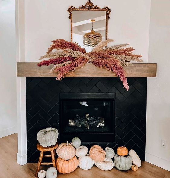 heirloom pumpkins stacked in front of the fireplace and spray painted pampas grass over the fireplace