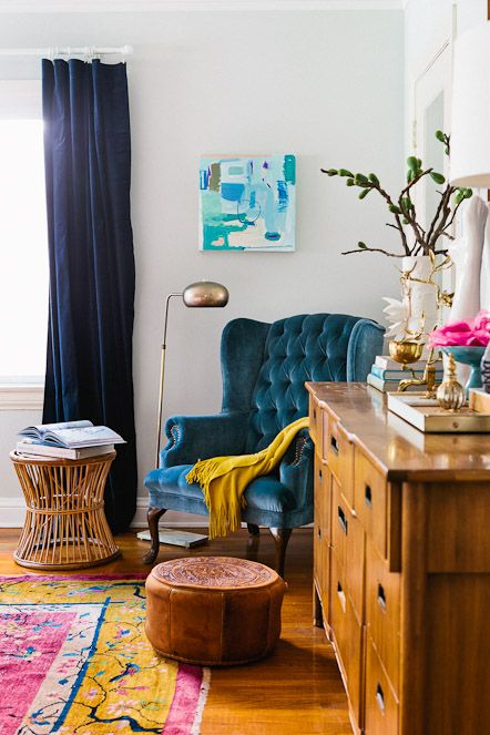 a colorful space with navy curtains, a bright rug, a blue velvet wingback chair, a wooden dresser