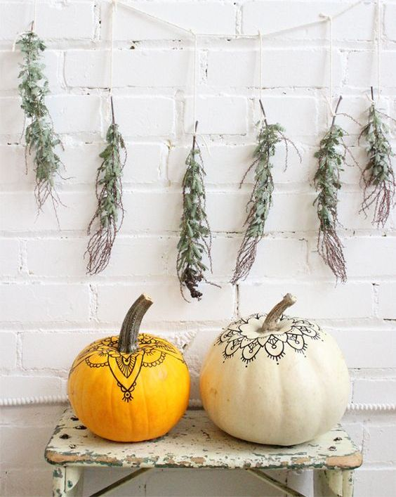 a duo of pumpkins decorated with a usual pen in a boho chic way look nice, a greenery garland adds a natural touch