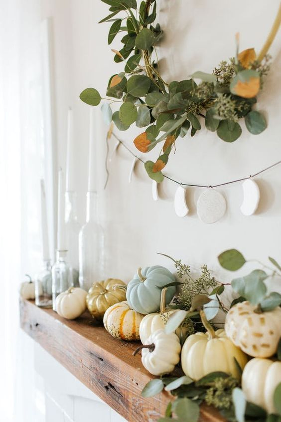 a modern rustic mantel with eucalyptus, natural pumpkins, a greenery wreath over them and a moon phase hanging