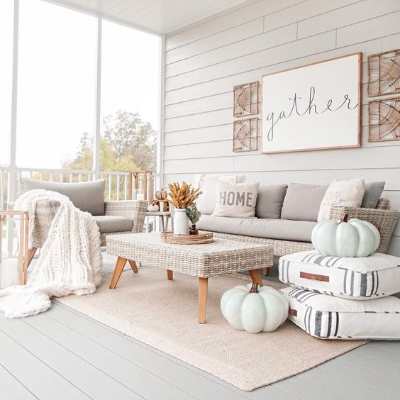 an elegant and cozy neutral porch stylish with neutral furniture, textiles, chalk painted pumpkins, some fall leaf arrangements and a sign