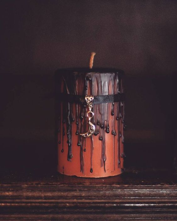 a chic witchy candle in rust, with black drip, a ribbon with a lunar pendant in gold is a very refined idea