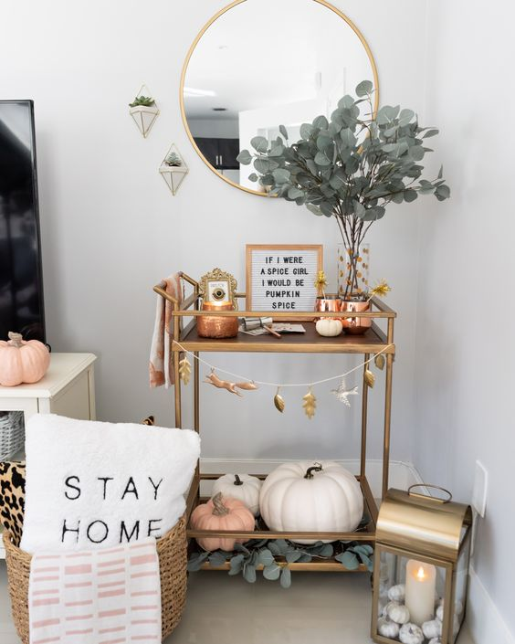 a modern fall bar cart with greenery in a vase, faux pumpkins, a fall leaf bunting and copper candleholders