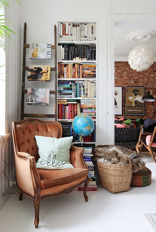 a cozy and chic reading nook with a rust velvet wingback chair , a bookshelf and a basket with faux fur
