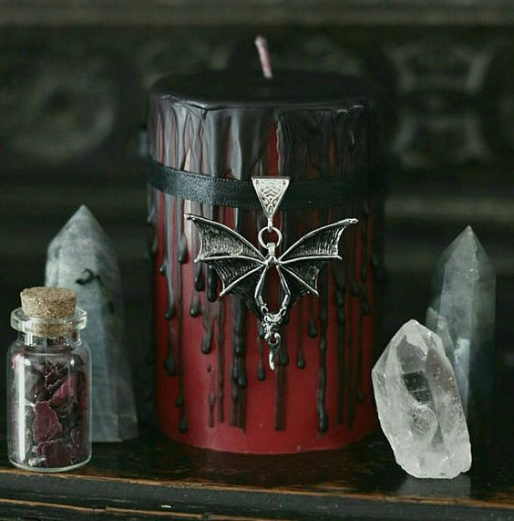 a red candle with black dripping, a black ribbon and a bat pendant will be a perfect decoration for a vampire Halloween party