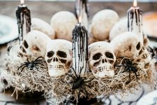 06 a Halloween centerpiece of a black stand, hay, skulls, spiders, candles with black drip is a stylish idea