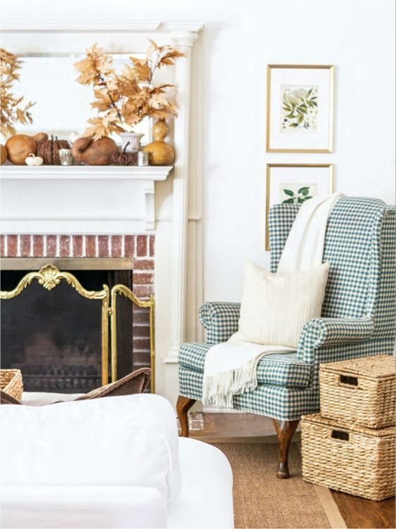 a fall farmhouse living room with a fireplace, a plaid wingback chair, chests, artworks and pumpkins and gourds