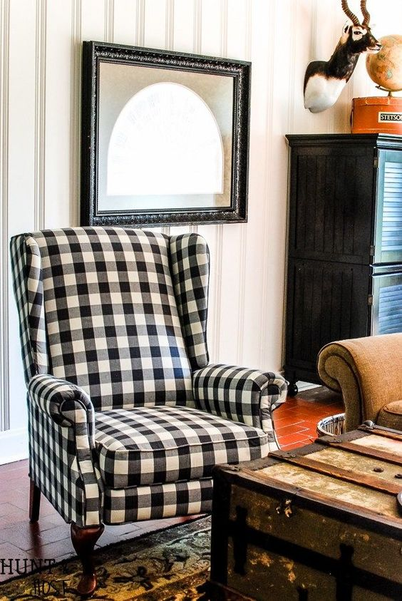 a French farmhouse nook with a plaid wingback chair, a chest and an artwork for a stylish rustic look