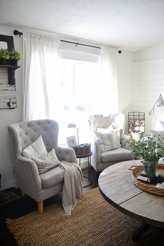 a neutral farmhouse space with dove grey wingback chairs, pillows and blankets, a jute rug and a rough wooden table
