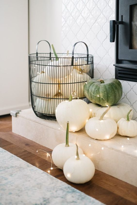 classy fall decor of a wire basket with white pumpkins, white and green pumpkins and lights is very cool and easy