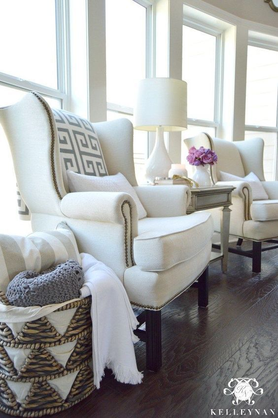 a neutral space done with elegant and cool white wingback chairs, pillows, a neutral side table and a lamp plus a basket with pillows