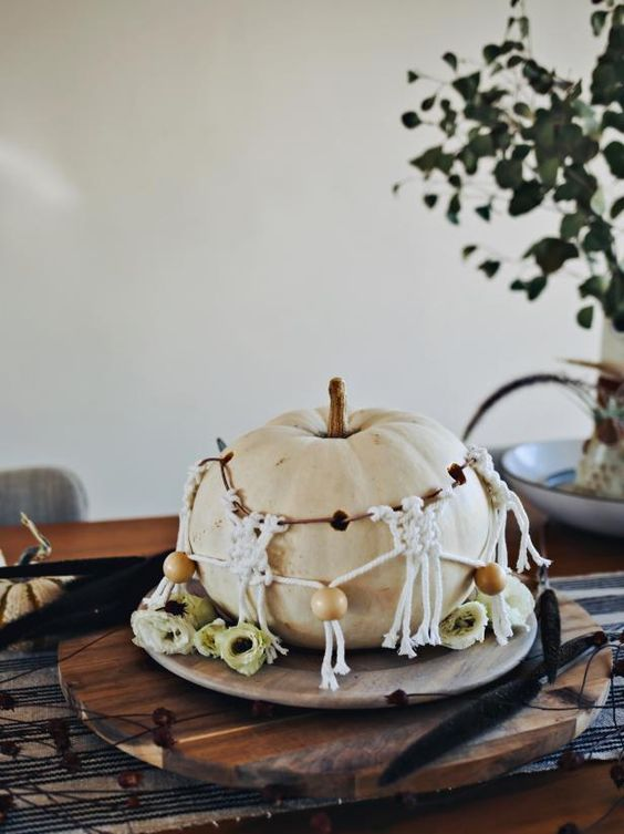 boho Halloween styling with a neutral pumpkin with macrame and beads plus some blooms and feathers
