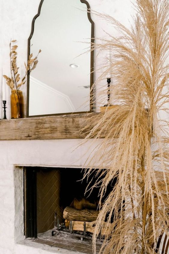 lush pampas grass in a vase and dried leaves in a vase add a modern fall feel to the space making it cooler