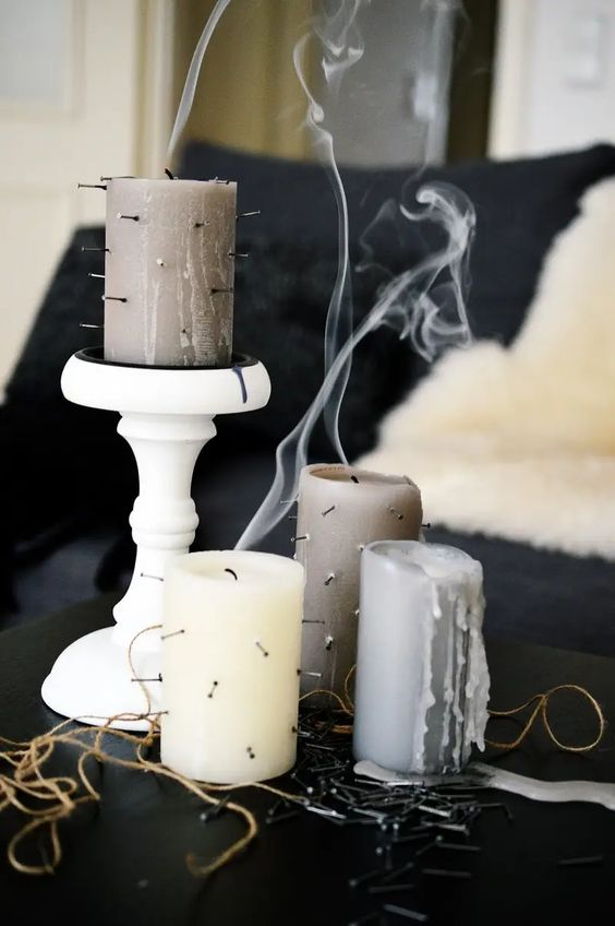 turn some basic neutral candles into chic Hallwoeen ones just adding nails and spikes, it's a very fast Halloween craft
