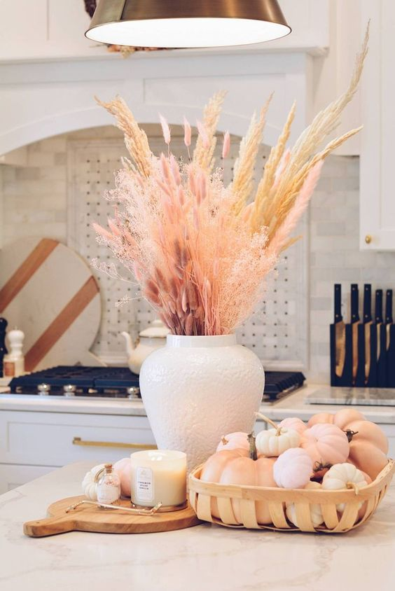 a stylish pastel fall arrangement of dried grasses and pink bunny tails, neutral and pink faux pumpkins and a candle in a glass