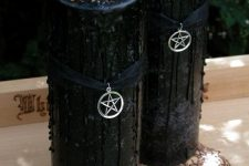 10 tall black candles with black drip and some crystals on top, black ribbons and star pendants for Halloween