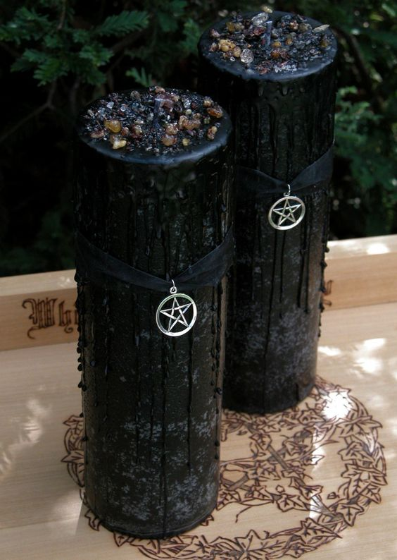 tall black candles with black drip and some crystals on top, black ribbons and star pendants for Halloween