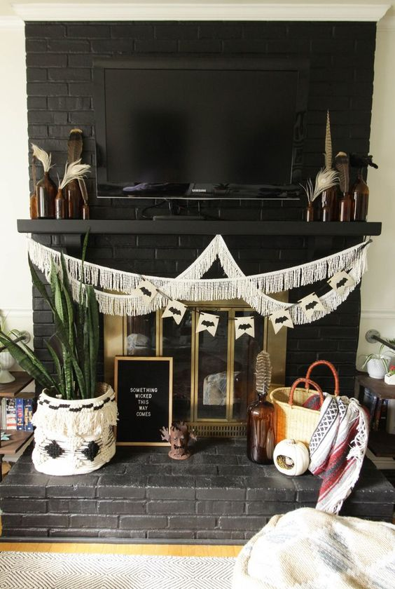 a boho Halloween fireplace with a fringe garland, potted succulents, feathers in bottles and pumpkins