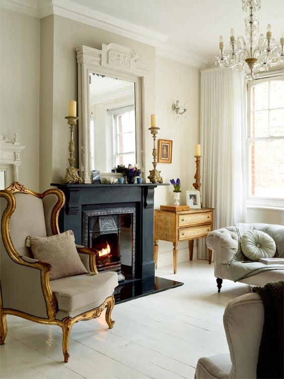 a refined Paris living room with a black fireplace, neutral furniture including an exquisite wingback chair, a refined chandelier