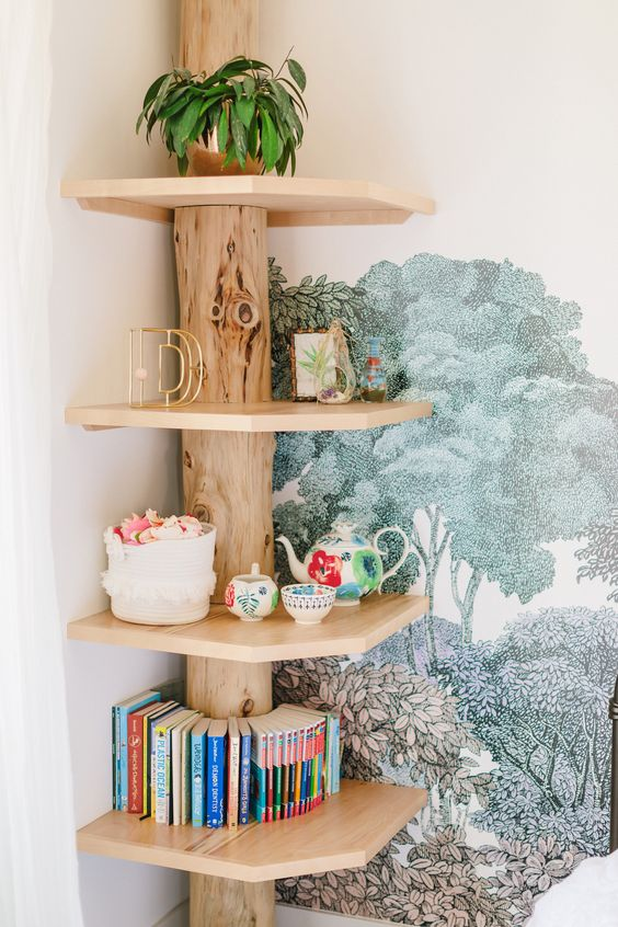 a rustic wooden shelf of a tree trunk and wooden shelves fits a corner perfectly and looks very warming and cozy