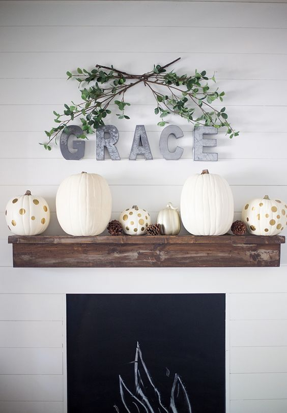 a stylish modern fall mantel with white and polka dot pumpkins and pinecones, metal letters and greenery