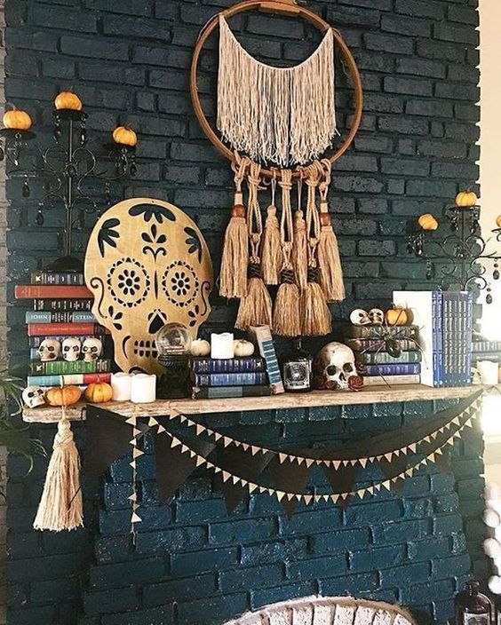 a boho Halloween mantel with a fringe and tassel hanging, a cutout skull, some garlands and tassels and mini pumpkins