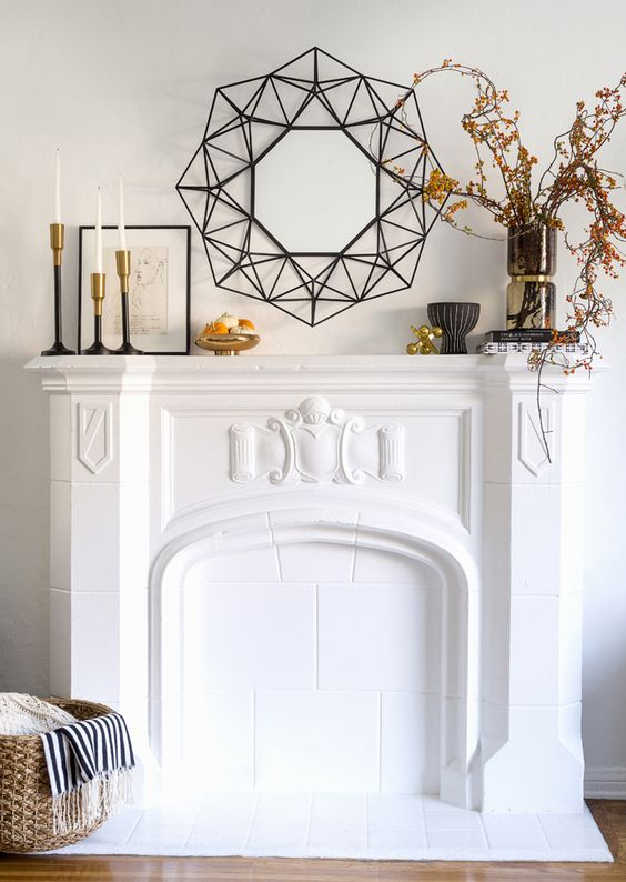 a stylish modern fall mantel with branches with berries, mini pumpkins on a gold stand and candles in candleholders